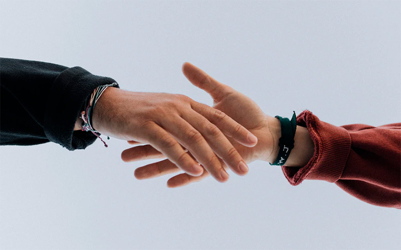 Two people reaching to hold hands